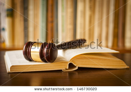 stock-photo-open-law-book-with-a-judges-gavel-resting-on-top-of-the-pages-in-a-courtroom-or-law-enforcement-146730020